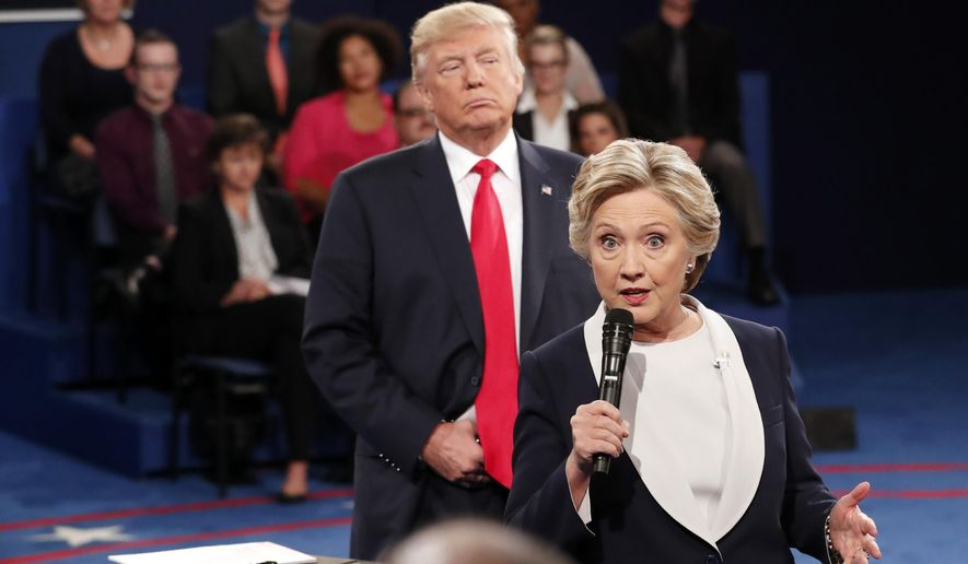In this Oct. 9, 2016, file photo, Democratic presidential nominee Hillary Clinton, right, speaks as Republican presidential nominee Donald Trump listens during the second presidential debate at Washington University in St. Louis, Sunday, Oct. 9, 2016. (Rick T. Wilking/Pool via AP) ** FILE **