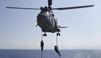 Lebanese army soldiers rappel down from a helicopter onto the deck of the Brazilian warship UNIAO, part of the UNIFIL Maritime force, during a joint training to apprehend the smuggling of illegal material, off the coast of Beirut, Lebanon, Wednesday, Aug. 23, 2017. The head of the U.N. peacekeepers in Lebanon says his force has no evidence that weapons are being illegally transferred in the country's south, rebuffing criticism the mission is failing to stem their spread. (AP Photo/Hussein Malla)