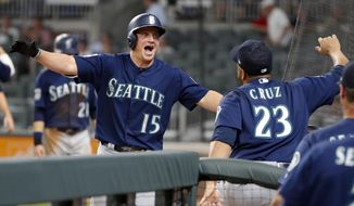 Seattle Mariners' Kyle Seager (15) celebrates with Nelson Cruz (23) after hitting a three-run home run in the eighth inning of a baseball game against the Atlanta Braves Wednesday, Aug. 23, 2017, in Atlanta. (AP Photo/John Bazemore)
