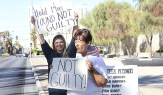 Cliven Bundy's daughter, Bailey Bundy Logue, left, and Margaret Houston of Logandale, Nev., wave signs in front of the Lloyd George U.S. Courthouse in Las Vegas after the not guilty verdict in the Bunkerville, Nev., standoff retrial Tuesday, Aug. 22, 2017.  A federal jury in Las Vegas has refused to convict four accused gunman in a 2014 standoff with federal authorities near the Nevada ranch of anti-government figure Cliven Bundy. (Michael Quine/Las Vegas Review-Journal via AP)