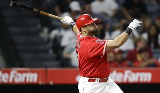 Los Angeles Angels' Albert Pujols watches his three-run home run against the Texas Rangers during the seventh inning of a baseball game in Anaheim, Calif., Tuesday, Aug. 22, 2017. (AP Photo/Chris Carlson)