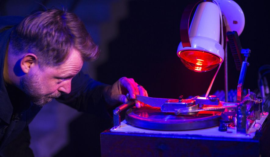 In this photo taken on Wednesday, Aug. 16, 2017, Paul Heartfield, one of London's most experienced and respected portrait artists starts to record on an X-ray film during a concert at the Bone Music exhibition at Garage Museum of Contemporary Art in Moscow, in Moscow, Russia . The exhibition describes a unique chapter in history of Soviet culture _ bootleg music recordings made on used X-ray film . (AP Photo/Alexander Zemlianichenko)