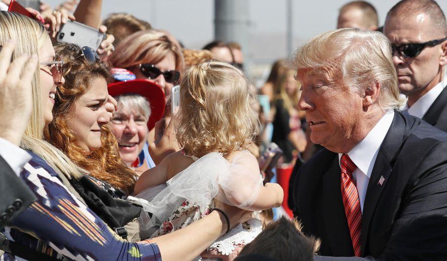 President Donald Trump struggles to hold a baby as he greets supporters as he arrives in Reno, Nev., Wednesday, Aug. 23, 2017. (AP Photo/Alex Brandon) ** FILE **