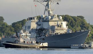 In this July 11, 2017 photo provided by U.S. Navy Office of Information, the Valiant-class yard tugboat Menominee (YT 807) assists the Arleigh Burke-class guided-missile destroyer USS Fitzgerald (DDG 62) as it moves to Dry Dock 4 at Fleet Activities (FLEACT) Yokosuka, Japan, to continue repairs and assess damage sustained from its June 17 collision with a merchant vessel. Poor seamanship and flaws in keeping watch contributed to a collision between the Navy destroyer and a commercial container ship that killed seven sailors, Navy officials said, announcing that the warship captain will be relieved of command and more than a dozen other sailors will be punished. Adm. William Moran, the vice chief of naval operations, told reporters Thursday, Aug. 17, 2017, that the top three leaders aboard the USS Fitzgerald, which was badly damaged in the collision off the coast of Japan, will be removed from duty aboard the ship. (Mass Communication Specialist 1st Class Peter Burghart/U.S. Navy photo via AP)