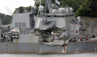 FILE - In this June 18, 2017, file photo, the damaged USS Fitzgerald is docked at the U.S. Naval base in Yokosuka, southwest of Tokyo, after colliding with Philippine-flagged container ship ACX Crystal off Japan.  On June 17, 2017, seven sailors died after a container ship collided with the USS Fitzgerald guided-missile destroyer off Japan. (AP Photo/Eugene Hoshiko, File)