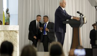 Secret service agents confer as Vice President Mike Pence speaks at Our Lady of Guadalupe Catholic Church, Wednesday, Aug. 23, 2017, in Doral, Fla. Pence met with members members of the Venezuelan exile community. (AP Photo/Lynne Sladky)