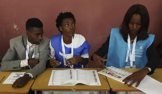 Voter officials at their stations during presidential elections in Luanda, Angola, Wednesday, Aug. 23, 2017. Defense Minister, Joao Lourenco, is the front-runner to succeed President Jose Eduardo dos Santos, who will step down after 38-years in power in an oil-rich country. (AP Photo/Bruno Fonseca)