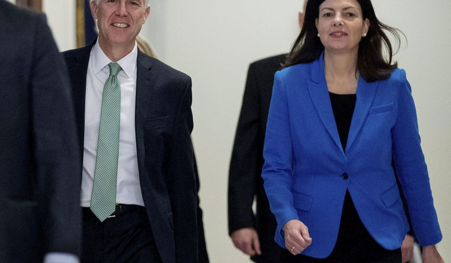 FILE - In this Feb. 14, 2017, file photo, former New Hampshire Sen. Kelly Ayotte, right, accompanies Supreme Court Justice nominee Neil Gorsuch for a meeting on Capitol Hill in Washington. Ayotte said it's time for politicians in Washington to put aside the debate over climate change and focus on getting things that could further efforts to expand renewable energy and other clean energy solutions. Ayotte, who last month became a senior adviser with the conservative Citizens for Responsible Energy Solutions, said she believes the science on climate change is settled. (AP Photo/Andrew Harnik, File)