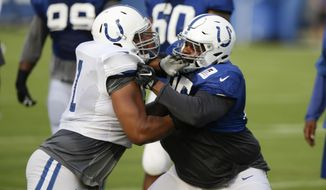 File-This Aug. 1, 2017, file photo shows Indianapolis Colts offensive guard Denzelle Good, left, blocking defensive tackle Johnathan Hankins (95) during practice at the NFL team's football training camp in Indianapolis. (AP Photo/Michael Conroy, File)