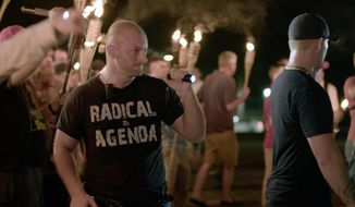"In this Friday, Aug. 11, 2017, file image made from a video provided by Vice News Tonight, Christopher Cantwell attends a white nationalist rally in Charlottesville, Va. On Wednesday, Aug. 23, Cantwell, a white nationalist, turned himself in to face three felony charges in Virginia, authorities said. Cantwell was wanted by University of Virginia police on two counts of the illegal use of tear gas or other gases and one count of malicious bodily injury with a ""caustic substance,"" explosive or fire. (Vice News Tonight via AP, File)"