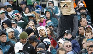 """FILE - In this Nov. 22, 2015, file photo, a fan wears a paper bag on his head in the stands of Lincoln Financial Field during the second half of an NFL football game between the Philadelphia Eagles and the Tampa Bay Buccaneers in Philadelphia. The obituary for an Eagles fan who died Aug. 18, 2017, stated that he wanted 8 members of the team to serve as pallbearers so the Eagles could let him down """"one last time."""" (AP Photo/Julio Cortez, File)"""