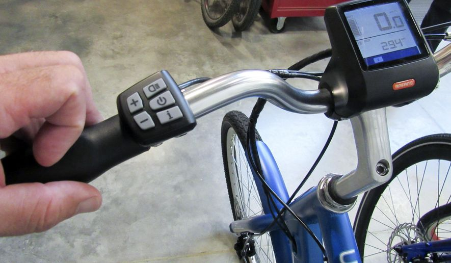 In this Aug. 16, 2017 photo, the controls for a Schwinn e-bike are on the left handle bar and allow the rider to adjust the degree of assistance from the bike's battery-powered motor in Madison, Wis. Baby Boomers who cruised the streets of America between the 1950s and 1970s on the popular brand of bikes will soon have a few new Schwinn rides that come with classic-sounding names and evolving technology. (Barry Adams/Wisconsin State Journal via AP)