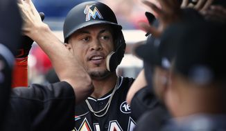 Miami Marlins' Giancarlo Stanton is congratulated after he hit a home run against the Philadelphia Phillies during the third inning of a baseball game Thursday, Aug. 24, 2017, in Philadelphia, Pa. (AP Photo/Rich Schultz)