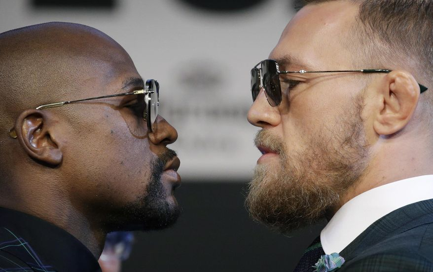 Floyd Mayweather Jr., left, and Conor McGregor pose for photographers during a news conference Wednesday, Aug. 23, 2017, in Las Vegas. The two are scheduled to fight in a boxing match Saturday in Las Vegas. (AP Photo/John Locher)