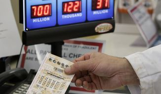 A customer is handed a Powerball ticket in Omaha, Neb., Wednesday, Aug. 23, 2017. Lottery officials said the grand prize for Wednesday night's drawing has reached $700 million. The second -largest on record for any U.S. lottery game. (AP Photo/Nati Harnik)