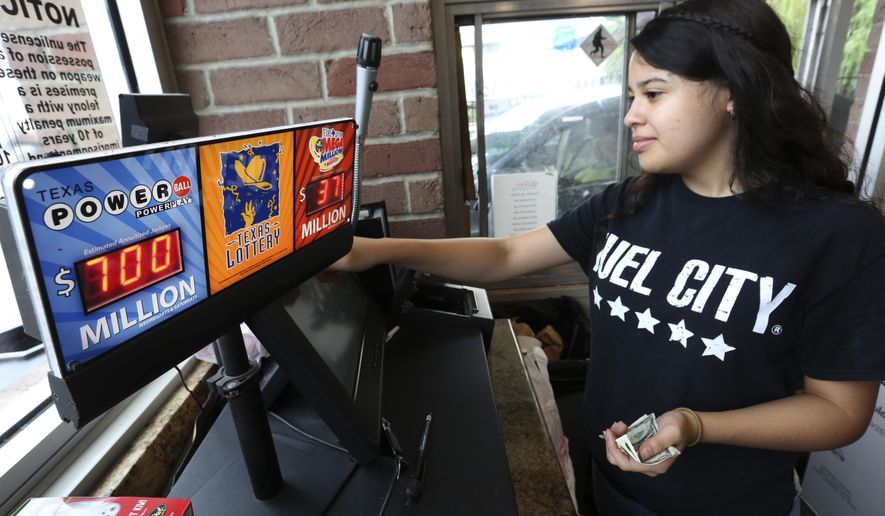 Anahi Medrano sells a Powerball lottery ticket at a convenience store in Dallas Wednesday, Aug. 23, 2017. Lottery officials said the grand prize for Wednesday night's drawing has reached $700 million. The second -largest on record for any U.S. lottery game. (AP Photo/LM Otero)