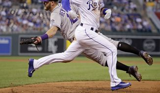 Colorado Rockies first baseman Mark Reynolds dives for but misses the throw allowing Kansas City Royals' Whit Merrifield to get on base and score a runner on a throwing error by shortstop Trevor Story during the second inning of a baseball game Wednesday, Aug. 23, 2017, in Kansas City, Mo. (AP Photo/Charlie Riedel)