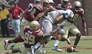File-This Sept. 10, 2016, file photo shows Florida State's Brian Burns stripping the ball from Charleston Southern's Robert Mitchell in the second half of an NCAA college football game, in Tallahassee, Fla. Florida State's defense returns nine starters to a unit that struggled the first half of last season before rounding into form. Defensive coordinator Charles Kelly is hoping that the lessons the No. 3 Seminoles learned last season pay off. They will find out quickly since the opener is against top-ranked Alabama. (AP Photo/Steve Cannon)