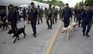 Security officers lead sniffer dogs outside Supreme Court ahead the delivery of a verdict on charges accusing Thailand's former Prime Minister Yingluck Shinawatra of negligence in implementing a rice subsidy in Bangkok Thailand, Friday, Aug 25, 2017.  Police stood guard Friday morning as Thailand's Supreme Court prepared to rule on whether Shinawatra was guilty of criminal negligence for implementing a rice subsidy program that cost the government as much as $17 billion. (AP Photo/Gemunu Amarasinghe)