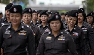 Police officers deploy to positions outside Supreme Court ahead the delivery of a verdict on charges accusing Thailand's former Prime Minister Yingluck Shinawatra of negligence in implementing a rice subsidy in Bangkok Thailand, Friday, Aug 25, 2017. Police stood guard Friday morning as Thailand's Supreme Court prepared to rule on whether Yingluck was guilty of criminal negligence for implementing a rice subsidy program that cost the government as much as $17 billion. (AP Photo/Gemunu Amarasinghe)