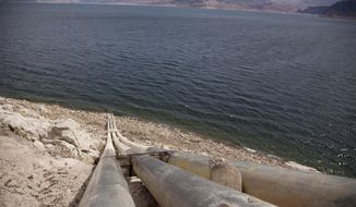 FILE - This March 23, 2012, file photo shows pipes extending into Lake Mead well above the high water mark near Boulder City, Nev. A federal judge tapped the brakes Thursday, Aug. 24, 2017, but didn't stop a proposal for a massive and expensive water pipeline to draw underground water from rural valleys in arid eastern Nevada to supply the growing Las Vegas metropolitan area. (AP Photo/Julie Jacobson, File)