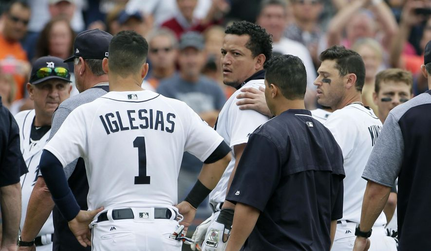 Detroit Tigers' Miguel Cabrera looks back at the New York Yankees as he is guided off the field by teammate Ian Kinsler, right, and Jose Iglesias (1) following a bench-clearing fight during the sixth inning a of a baseball game Thursday, Aug. 24, 2017, in Detroit. (AP Photo/Duane Burleson)