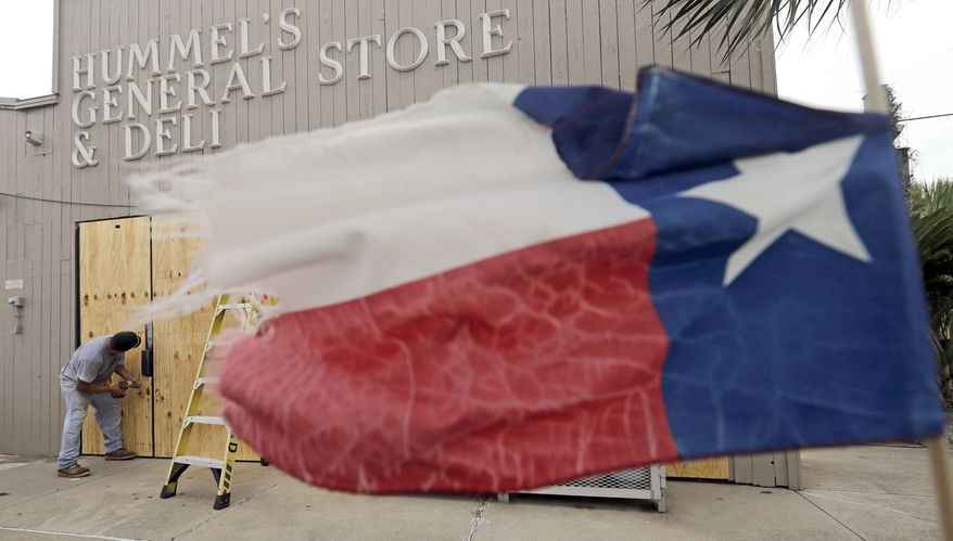 Ramon Lopez boards up windows of a business in Galveston, Texas as Hurricane Harvey intensifies in the Gulf of Mexico Friday, Aug. 25, 2017. Harvey is forecast to be a major hurricane when it makes landfall along the middle Texas coastline. (AP Photo/David J. Phillip)