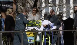 In this image made from video, injured students are attended to at Australian National University in Canberra, Australia, Friday, Aug. 25, 2017. A man was detained by police after assaulting four students on Friday in a university classroom with what one witness described as a bat, university officials and police said. (Australian Broadcasting Corporation via AP)