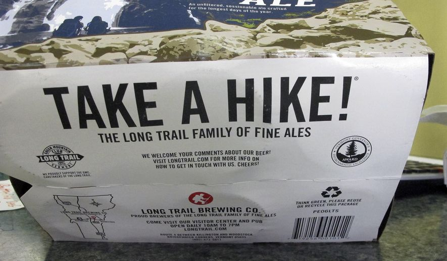 """A label with the slogan """"Take a Hike"""" is displayed on the bottom of a six-pack of Long Trail Brewing Co., beer at Elm Street Market, Friday, Aug. 25, 2017, in Montpelier, Vt. The beer company sued Burton Corporation over use of the slogan on the snowboard company's apparel. Long Trail said Friday the two companies had worked out an amicable resolution. (AP Photo/Lisa Rathke)"""