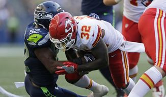 Kansas City Chiefs running back Spencer Ware is tackled by Seattle Seahawks linebacker Terence Garvin (52) during the first half of an NFL football preseason game, Friday, Aug. 25, 2017, in Seattle. Ware left the field with an injury after the play. (AP Photo/John Froschauer)