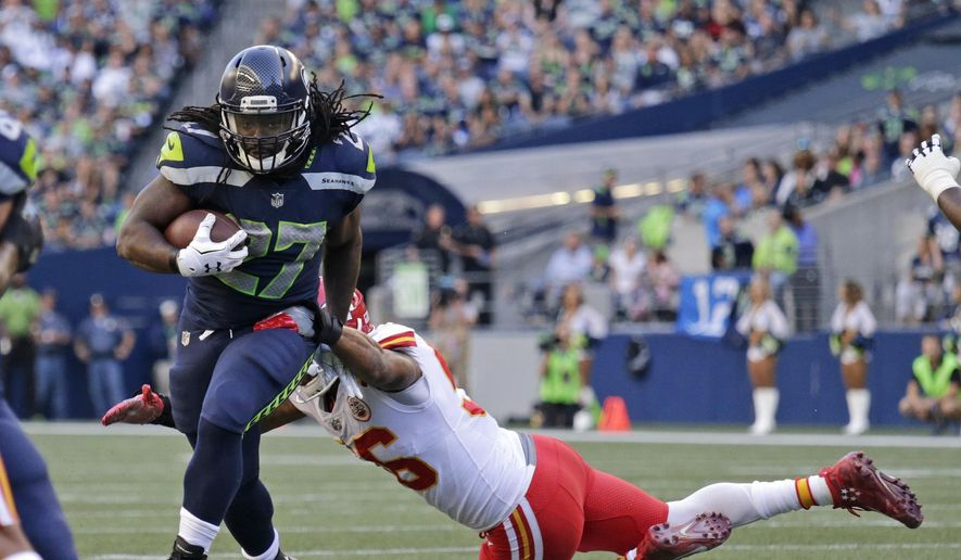 Seattle Seahawks running back Eddie Lacy, left, breaks a tackle by Kansas City Chiefs inside linebacker Derrick Johnson, right, during the first half of an NFL football preseason game, Friday, Aug. 25, 2017, in Seattle. (AP Photo/John Froschauer) **FILE**