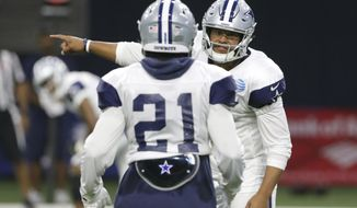 Dallas Cowboys quarterback Dak Prescott, right, gives directions to running back Ezekiel Elliott (21) during an NFL football camp practice in Frisco, Texas, Tuesday, Aug. 22, 2017. (AP Photo/LM Otero)