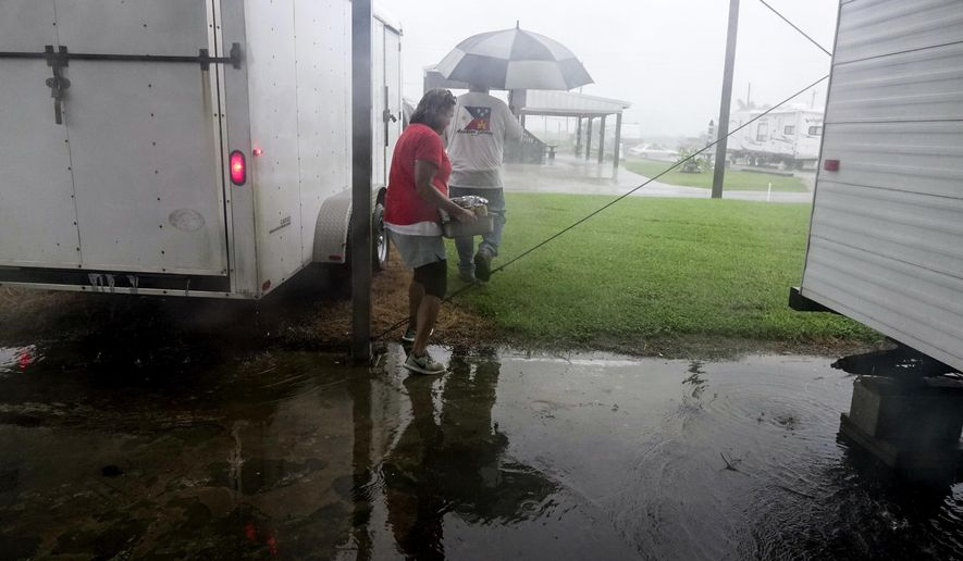 Chris and Lisa Broussard, of Abbeville, remove items from their trailer as early rain squalls from Hurricane Harvey in Holly Beach, La. Friday, Aug. 25, 2017. (Lee Celano /The Daily Advertiser via AP)