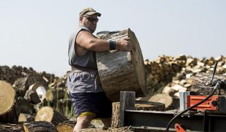 """In this Thursday, Aug. 3, 2017 photo, volunteer Jeff Shields lifts a stump over to a log splitter in Coeur d'Alene, Idaho. Shields, a former mill worker, volunteers about 20 hours a week for Elder Help. Nicknamed """"Rambo"""" from his days of working in local lumber mills, Shields' mental and physical toughness has crushed his disabilities of blindness and lack of hearing to the tune of handling up to 450-pound pieces of wood to split for residents in need.  (Loren Benoit /Coeur D'Alene Press via AP)"""