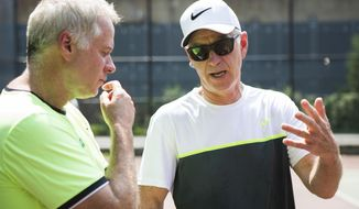 In this Tuesday, Aug. 22, 2017 photo Patrick and John McEnroe chat during scholarship tryouts for children ages 6 to 12 who are interested in attending the John McEnroe Tennis Academy in New York. (AP Photo/Michael Noble Jr.)