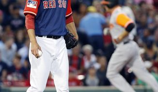 Baltimore Orioles' Mark Trumbo, right, rounds the bases on his solo home run behind Boston Red Sox's Rick Porcello during the second inning of a baseball game in Boston, Friday, Aug. 25, 2017. (AP Photo/Michael Dwyer)