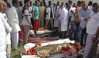 Somalis observe bodies which were brought to and displayed in the capital Mogadishu, Somalia Friday, Aug. 25, 2017. A number of civilians are dead after a raid by foreign and Somali forces on a farm in Barire village in southern Somalia, according to the deputy governor of Lower Shabelle region. (AP Photo/Farah Abdi Warsameh)
