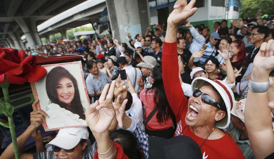 Supporters of Thailand's former Prime Minister Yingluck Shinawatra dance outside the Supreme Court after Yingluck failed to show up to hear a verdict in Bangkok Thailand, Friday, Aug. 25, 2017. Thailand's Supreme Court said Friday it will issue an arrest warrant for Yingluck after she failed to show up for a contentious trial verdict in which she could face a 10-year prison term for alleged negligence in overseeing a money-losing rice subsidy program. (AP Photo/Wason Wanichakorn)