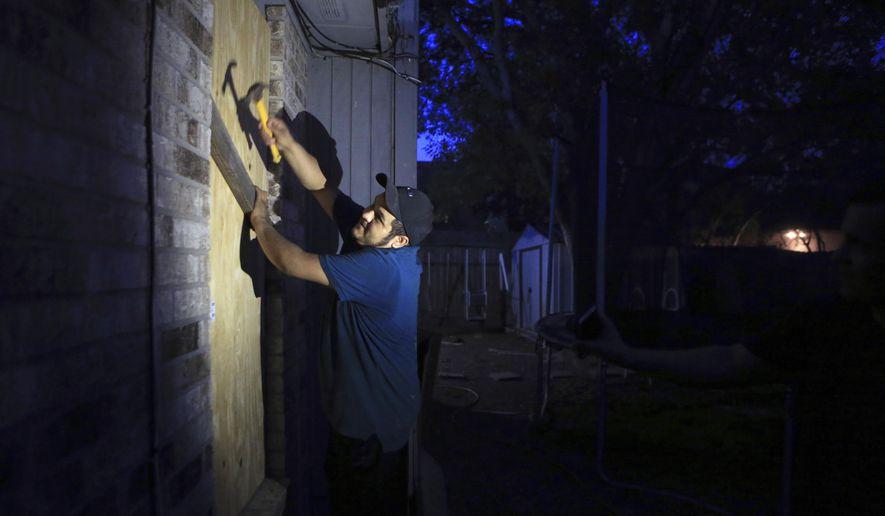 Mauro Eligio boards up his home on the Southside of Corpus Christi, Texas, on Thursday, Aug. 24, 2017, in preparation of Hurricane Harvey. (Rachel Denny Clow/Corpus Christi Caller-Times via AP)