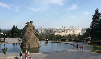The construction of a 2018 World Cup stadium, background, is seen behind the Battle of Stalingrad memorial, foreground, in Volgograd, formerly Stalingrad, about 900 kilometers (550 miles) southeast of Moscow, Russia, Wednesday, Aug. 23, 2017. Nazi shells and Soviet soldiers' bodies are all part of the job for Sergei Kamin, who oversees construction of a 2018 World Cup stadium in Volgograd _ formerly known as Stalingrad. The regional governor hopes Germany could be drawn to play in the city during the World Cup as a symbol of peace.(AP Photo/James Ellingworth)