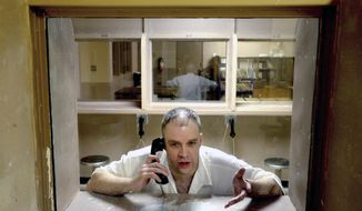 """In this Friday, March 18, 2016 photo. inmate Brad Dunn sits behind glass during an interview at the Texas Department of Criminal Justice's Mark W. Michael Unit in Tennessee Colony, Texas. Congress is close to finalizing changes to the nation's emergency dialing system inspired by a girl's struggle to call 911 as her mother lay dying from stab wounds in a Texas hotel room. """"Kari's Law"""" was named after Kari Hunt Dunn, who was slain in 2013 when Brad Dunn, her estranged husband stormed into her hotel room and stabbed her multiple times while her children watched. (Kevin Green/The News-Journal via AP)"""