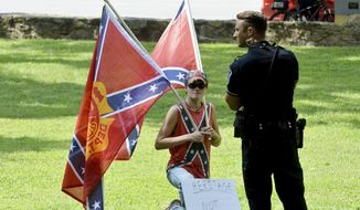 "A group of people counter protest a sit-in underway Saturday, Aug. 26, 2017, at a Confederate statue called ""Silent Sam"" on the University of North Carolina campus, in Chapel Hill, N.C. The counter-protesters carried Confederate battle flags and kept their distance from the statue sitting besides UNC police officers. (Bernard Thomas/The Herald-Sun via AP) **FILE**"