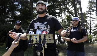 Joey Gibson of the group Patriot Prayer, center, speaks at a news conference in Pacifica, Calif, Saturday, Aug. 26, 2017. Officials took steps to prevent violence ahead of a planned news conference by a right-wing group. (AP Photo/Marcio Jose Sanchez)