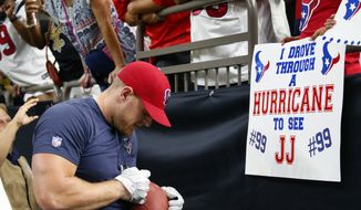 Houston Texans defensive end J.J. Watt signs autographs for fans holding sings referencing Hurricane Harvey before an NFL football game against the New Orleans Saints in New Orleans, Saturday, Aug. 26, 2017. (AP Photo/Butch Dill)