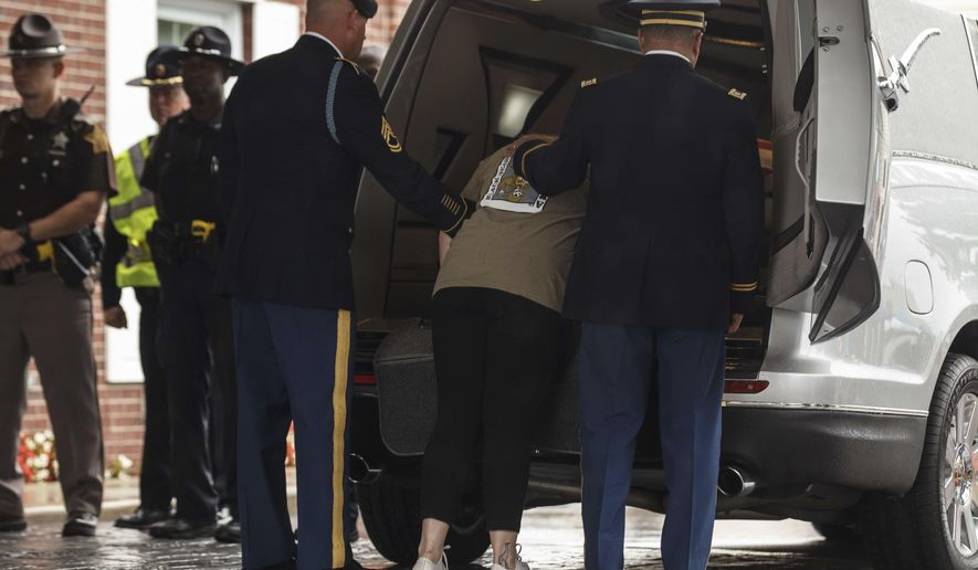 Whitney Hunter pays her respect to her fallen husband Sgt. Jonathon Hunter before an army ceremonial unit removes his casket from the back of a hearse at Barkes Weaver & Glick Funeral Home in Columbus, Ind., Tuesday, Aug. 22, 2017.   Hunter and 25-year-old Spec. Christopher Harris of Jackson Springs, N.C.,, were killed during an Aug. 2 attack on a NATO convoy. Both were with the 82nd Airborne Division at Fort Bragg, N.C.  Hunter's funeral is set for Saturday at Columbus East High School. (Mike Wolanin/The Republic via AP)