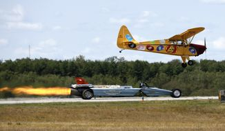 "Stunt pilot Kent Pietsch races the ""Smoke-N-Thunder Jet Car"" driven by Bill Braack at the Great State of Maine Air Show, Saturday, Aug. 26, 2017, at the former Brunswick Naval Air Station, in Brunswick, Maine. (AP Photo/Robert F. Bukaty)"