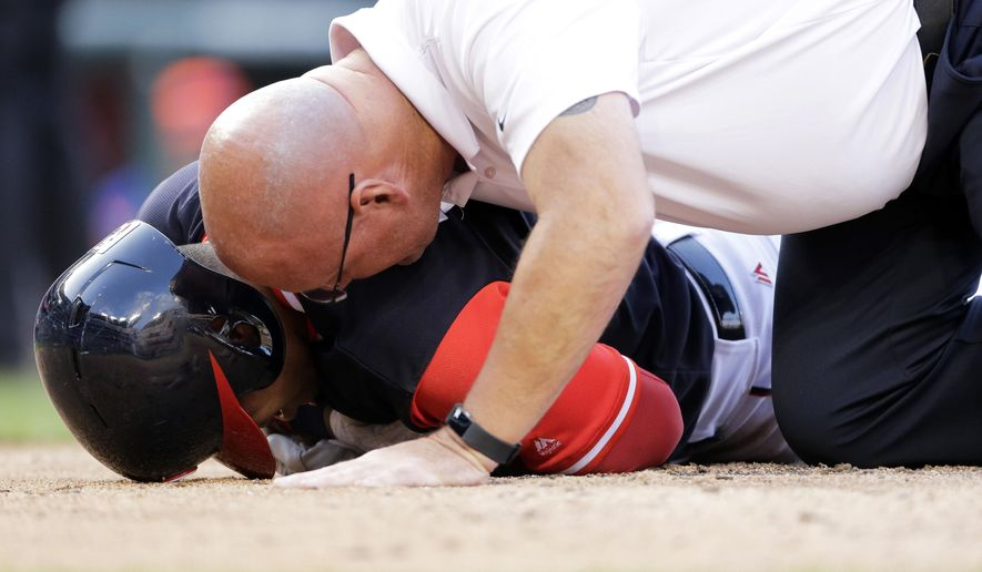 Washington Nationals athletic training director Paul Lassard, right, treats Adrian Sanchez after Sanchez was hit in the chest by a pitch during the eighth inning of a baseball game against the New York Mets, Saturday, Aug. 26, 2017, in Washington. (AP Photo/Mark Tenally)