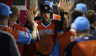 Houston Astros' George Springer, center, is greeted by teammates after scoring on a wild pitch by Los Angeles Angels starting pitcher Parker Bridwell during the sixth inning of a baseball game, Friday, Aug. 25, 2017, in Anaheim, Calif. (AP Photo/Jae C. Hong)