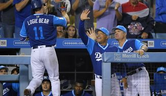 Los Angeles Dodgers' Logan Forsythe, left, is congratulated by manager Dave Roberts, center, and coach Bob Green after hitting a solo home run during the fourth inning of a baseball game against the Milwaukee Brewers, Friday, Aug. 25, 2017, in Los Angeles. (AP Photo/Mark J. Terrill)