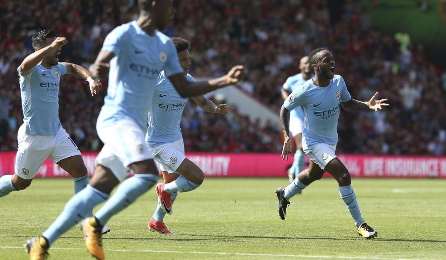 Manchester City's Raheem Sterling, right, celebrates scoring his side's second goal during the Premier League soccer match between AFC Bournemouth and Manchester City at the Vitality Stadium, Bournemouth, England. Saturday Aug 26, 2017. (Steve Paston/PA via AP)